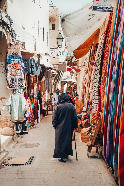 Fez Medina souk moroccan man colourful carpet